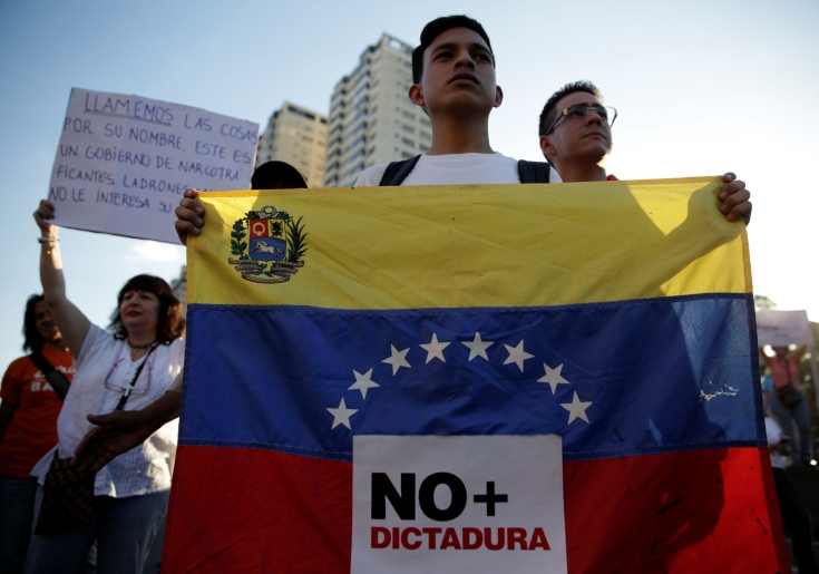 "An opposition supporter holds a Venezuelan flag with a sign that reads ""No more dictatorship"" during a protest against Venezuelan President Nicolas Maduro's government, in Caracas"